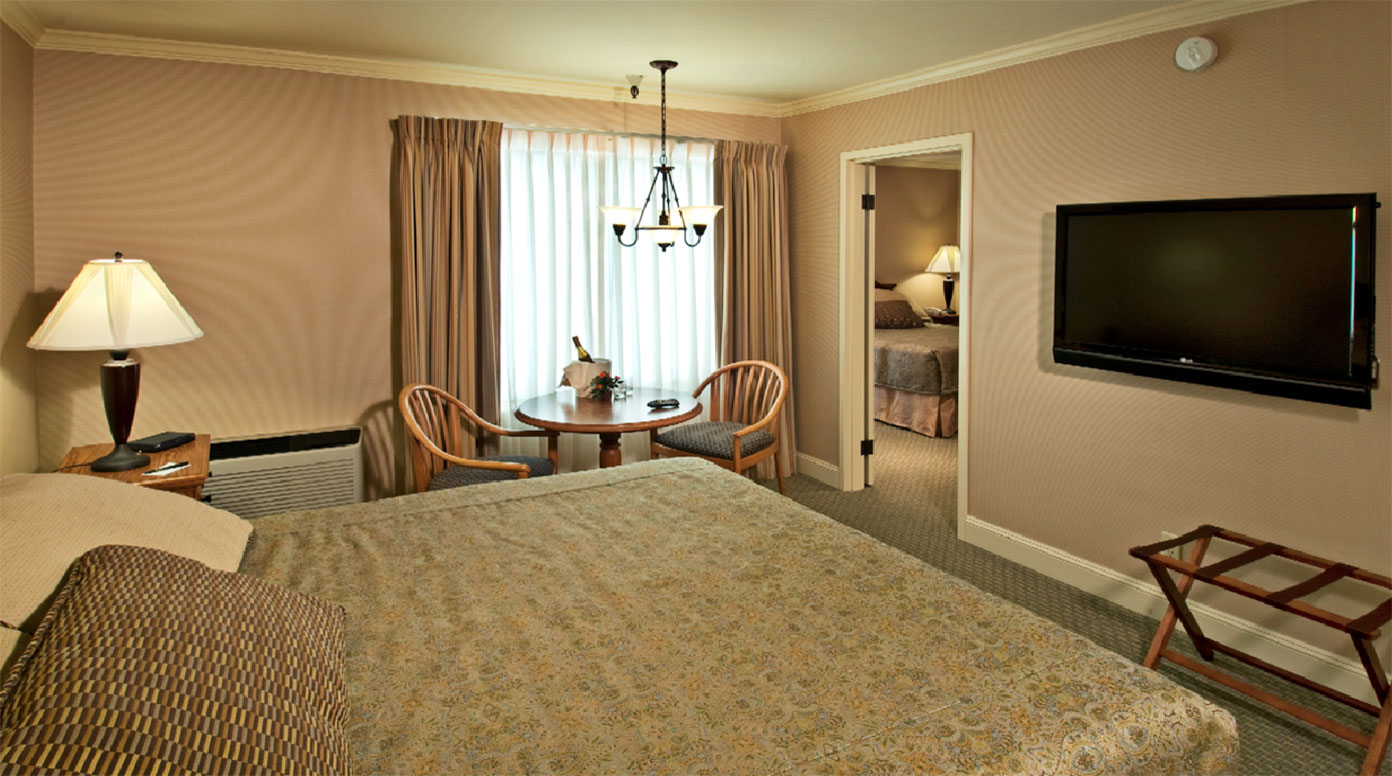 A room at the Columbus Inn with a twin bed, wall mounted flat screen TV and champagne chilling by the window.