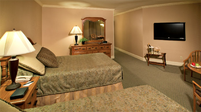 A room at the Columbus Inn with double twin beds, wall mounted flat screen TV and champagne chilling by the window.