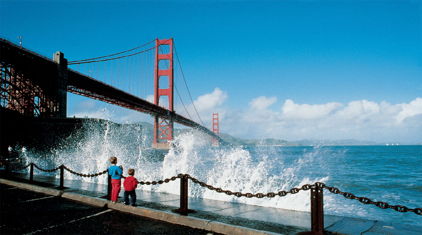 Two boys stand by the shore next to the Golden Gate Bridge
